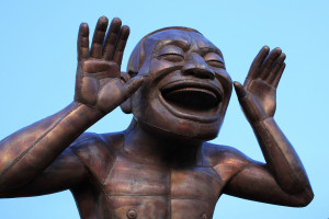 Image of sculpture featuring laughing figure