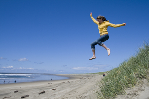 woman jumping off a sand dune
