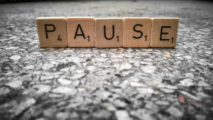 Scrabble tiles spelling the word 'Pause'.