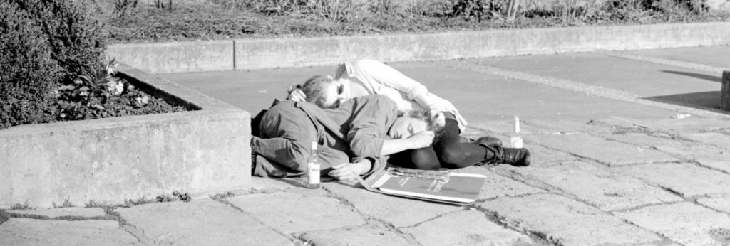 Two people snoozing on the pavement